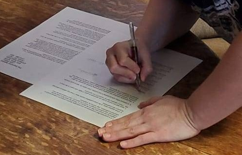 Image of Mae Thorn signing her contract agreement with her agent.